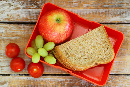 Lunch box with brown bread sandwich, red apple, grapes and cherry tomatoes