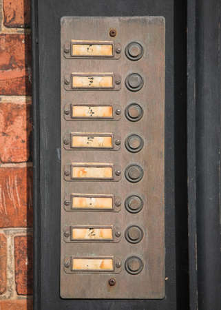 Row of numbered door bell buttons on a wall