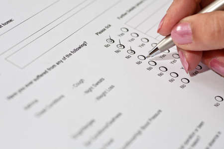 Photo pour Female job applicant completing a health questionnaire - image libre de droit