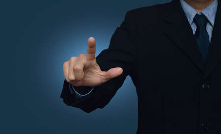 Foto de Businessman pointing to something or touching a touch screen on blue background - Imagen libre de derechos