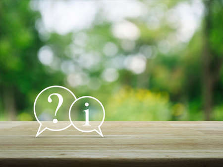 Photo pour Question mark and information chat icon on wooden table over blur green tree background, Customer support concept - image libre de droit