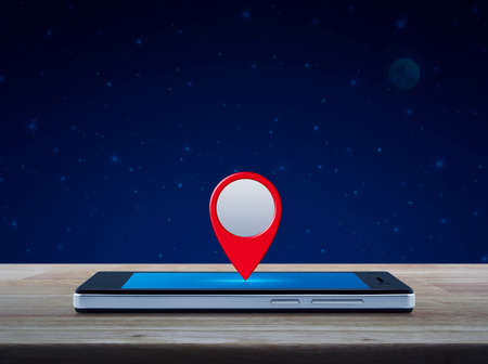 Map pin location button on modern smart phone screen on wooden table over fantasy night sky and moon, Map pointer navigation concept
