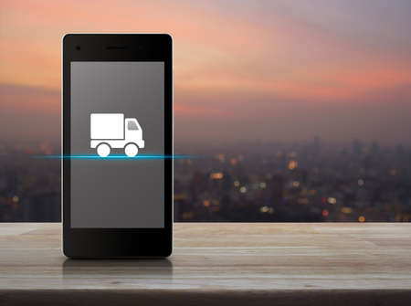 Photo pour Truck delivery flat icon on modern smart mobile phone screen on wooden table over blur of cityscape on warm light sundown, Business transportation online concept - image libre de droit