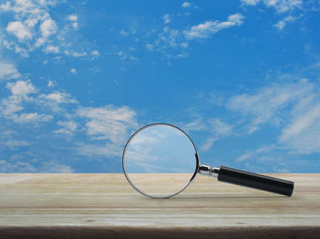 Photo for Magnifying glass on wooden table over blue sky with white clouds, Business analyzing concept - Royalty Free Image