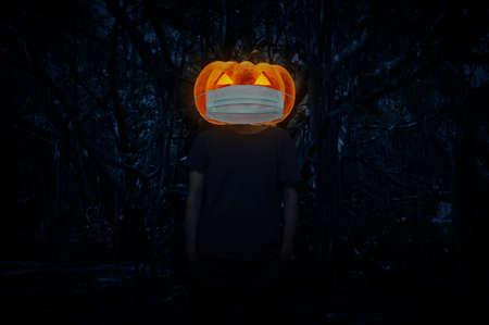 Foto de Halloween jack o lantern pumpkin wearing medical face mask standing over spooky dark forest with tree, leaves and vine, Halloween concept - Imagen libre de derechos