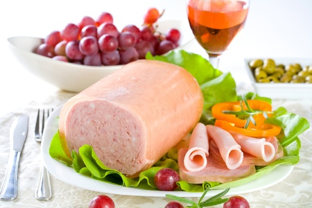 Luncheon meat, salad, olives and grapes