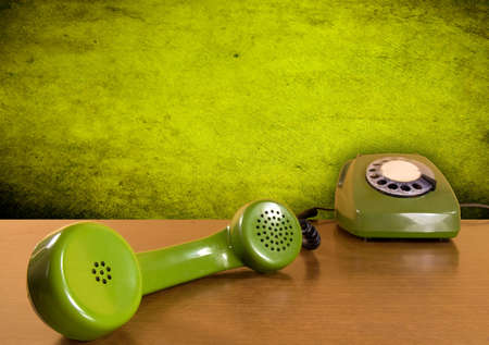 Vintage green telephone on the wooden table