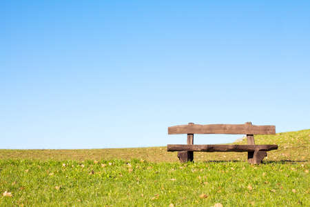 A calm place to rest and relax. An empty wooden bench  over a serene blue sky waiting for a hiker or casual walker to sit and rest.