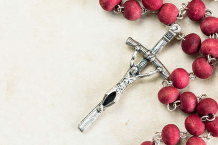 Catholic rosary on old paper background with copy-space