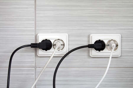 Electrical plugs connected into the wall sockets
