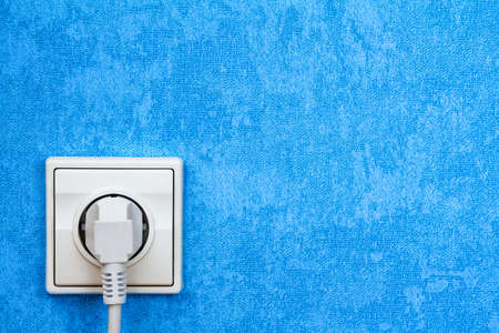 Electrical plug connected into the socket on blue wall