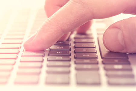 Photo for Single finger press button on laptop keyboard. Filtered image. - Royalty Free Image