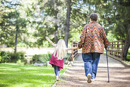 Photo pour Rear view of senior woman walking with little girl in park. Grandmother walking with cane holding granddaughter with hand - image libre de droit