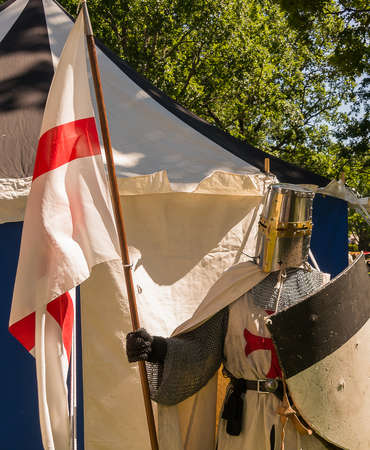 A person dresses up historically to mimic a knights templar in full armour standing in front of a white and blue tent holding a shield and flag.