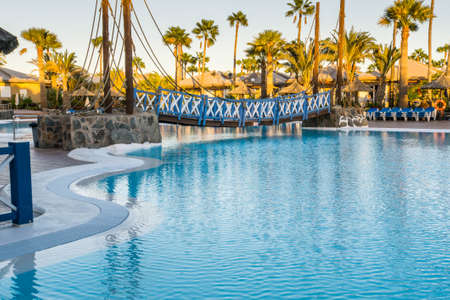 Mas Palomas Gran Canaria dec 08 2017 Cay beach princess hotel A suspension bridge painted white and blue hanging over a hotel pool leading between the bungalows and the hotel restaurant and bar area.