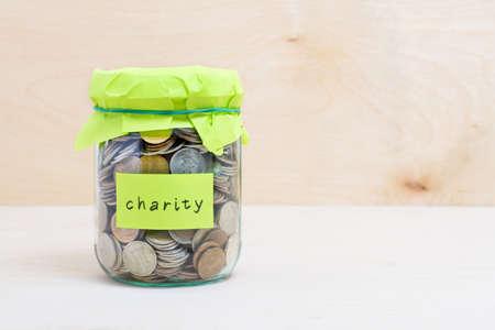 Photo pour Financial concept. Coins in glass money jar with charity label. Wooden background - image libre de droit