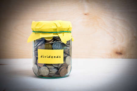 Financial concept. Coins in glass money jar with dividends label. Wooden background