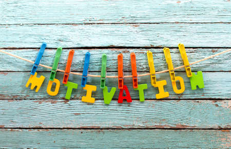 Photo for word motivation fasten clothespins on a rope behind a wooden background - Royalty Free Image