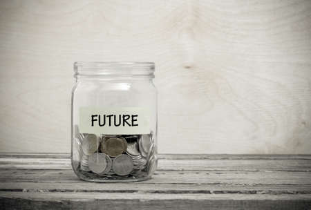 Label on a glass jar with the inscription - future. Glass jar with coins. Financial concept on wooden background