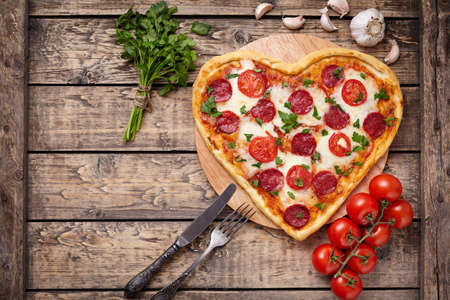 Photo pour Valentines day heart shaped pizza with pepperoni, cherry tomatoes, mozzarella and parsley on vintage wooden table background. Symbol of love. Rustic style, Top view. - image libre de droit