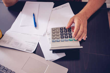 budget planning –Young man writing home budget with calculator
