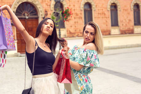 Photo pour women shopping. two young woman arguing at shopping in the city. - image libre de droit