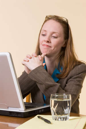 a business woman looking approvingly at her laptop computer screen