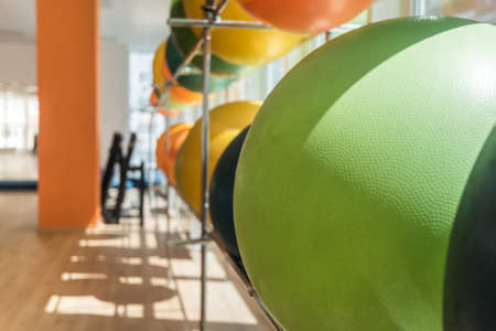Rack with exercise balls of various colors in modern fitness gym