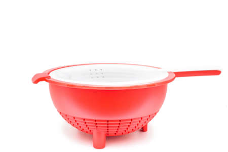 Red plastic colander isolated on white background