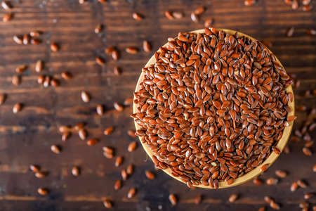 Photo pour Close up linseed in wooden bowl on wooden table - image libre de droit