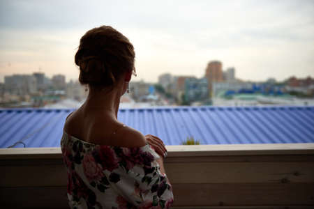 Back view of a dressed-up woman looking at the city from balcony