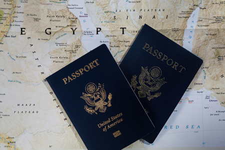 Two passports on a map of Egypt