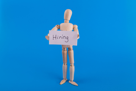 Wooden mannequin holding a hiring sign