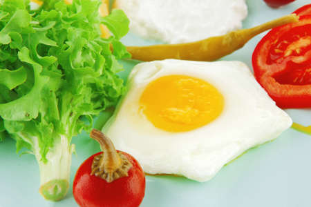 fried eggs with curd and salad on blue plateの写真素材