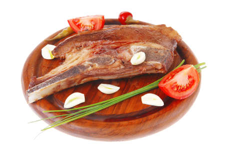 fresh hot roasted lamb meat fillet ready on red wooden plate with tomatoes, green pepper , and garlic isolated over white background