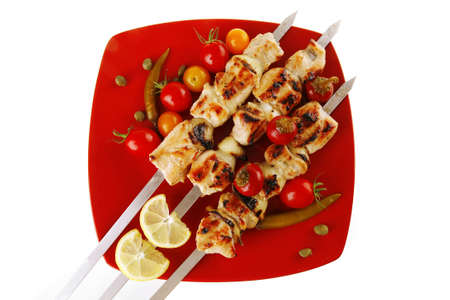 chicken shish kebab on red platter with vegetables