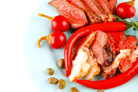 bacon meat slices served with tomatoes capers and red hot chili peppers on blue plate isolated on white