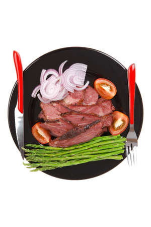 fresh sliced roast beef on black plate with cutlery and asparagus isolated on white background empty space for textの写真素材