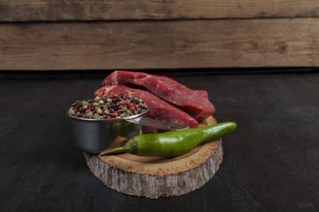 fresh raw beef piece fillet on middle size wooden plate with pepper and peppercorns in measuring spoon space for text on black background