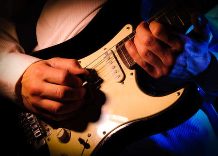 close up of a mans hands playing a guitar,