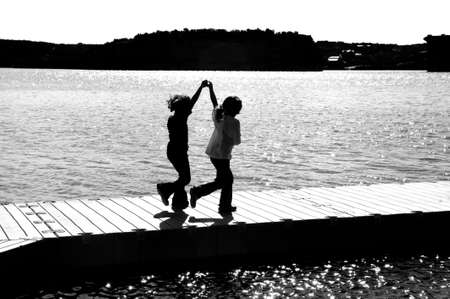 Image of a silhouette of two young girls playing on a dock