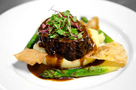 Image of a steak filet on a bed of mashed potatoes with asparagus, chips and gravy