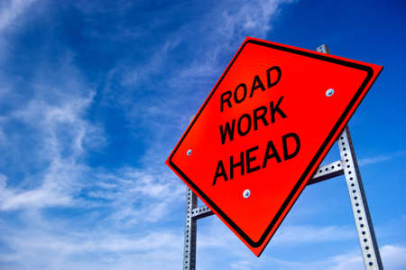 Photo for Image of a bright orange road work ahead sign against a blue sky with light clouds - Royalty Free Image