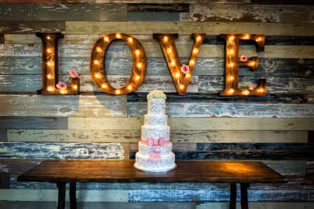 Foto de a wedding cake with the word love as sinage on a rustic background - Imagen libre de derechos