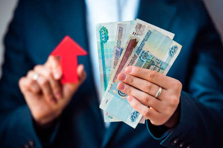 Business person holds roubles and red arrow