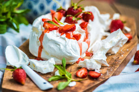 Classic british summer dessert called Eton Mess. Strawberries, crushed meringue and whipped cream on wooden board