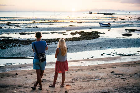 A young couple is watching a sunset at one of the beaches at Koh Samui, Thailand
