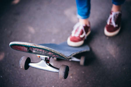 Young girl is holding her skateboard