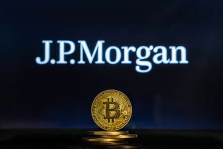 Bitcoin on a stack of coins with JP Morgan logo on a laptop screen. Cryptocurrency and blockchain adoption getting mainstream. Slovenia - 02 24 2019