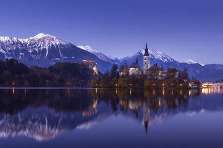 Photo pour Scenic view of lake Bled at winter night with castle rock and St Martin church under beautiful starry sky reflected in lake water - image libre de droit